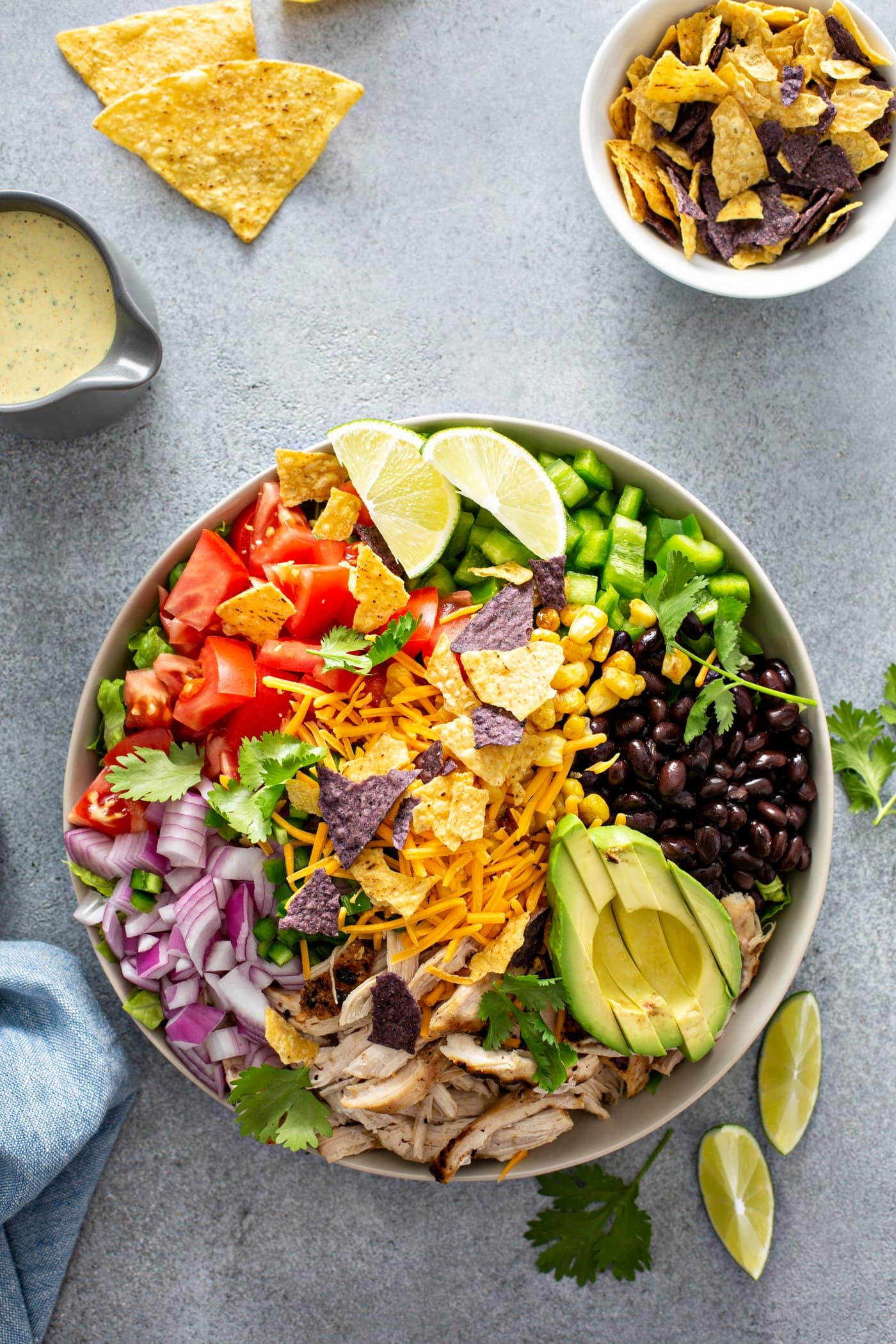 A chicken taco salad in a large bowl. It has chopped tomatoes, red onions, cheese, cilantro, lime wedges, chicken, corn, beans and peppers. There is also a sliced avocado. There are chips and a small container of dressing in the background.