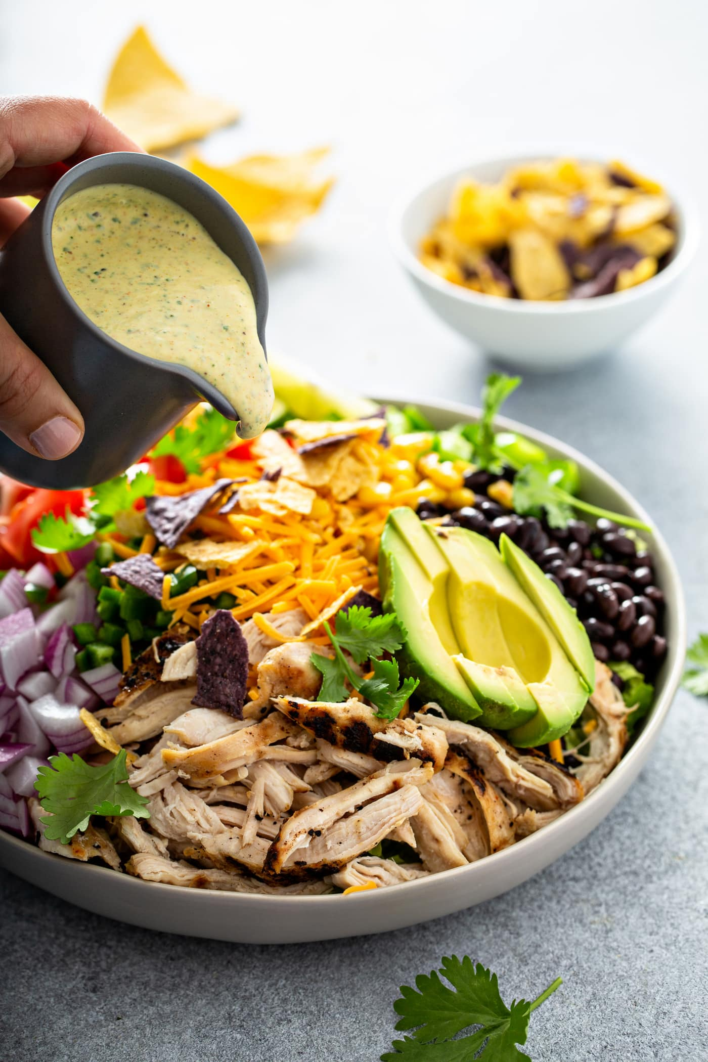 A chicken taco salad in a large bowl. It has chopped tomatoes, red onions, cheese, cilantro, lime wedges, chicken, corn, beans and peppers. There is also a sliced avocado. There are chips in the background and dressing is being poured over the salad.