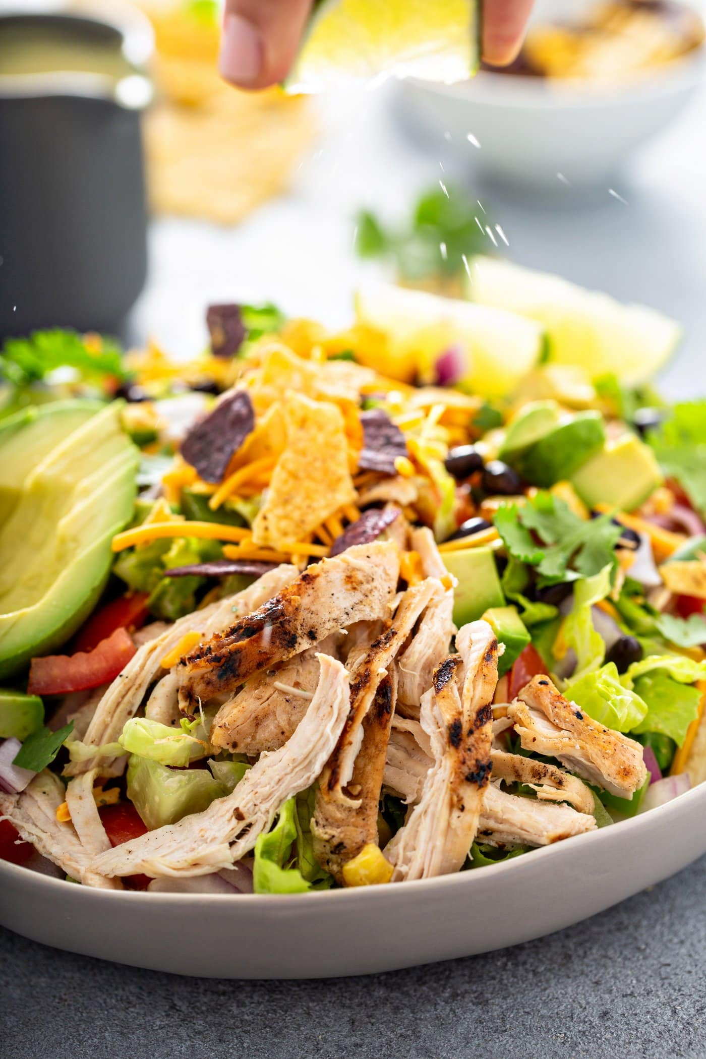A close-up of a large serving bowl filled with chicken taco salad. It contains shredded chicken, beans, corn, cilantro, tomatoes, red onions, and avocados. There are a couple of lime wedges next to the salad and chips and a container of dressing in the background.