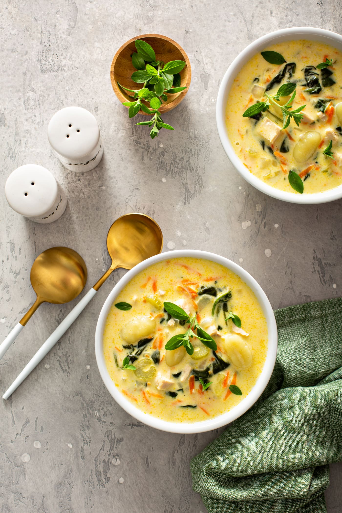Two bowls of copycat Olive Garden chicken gnocchi soup. The soup has shredded carrots, gnocchi, celery and spinach in a creamy soup. Fresh herbs are sprinkled on top, and two soup spoons, salt and pepper shakers, and a green napkin are on the table next to the soup.