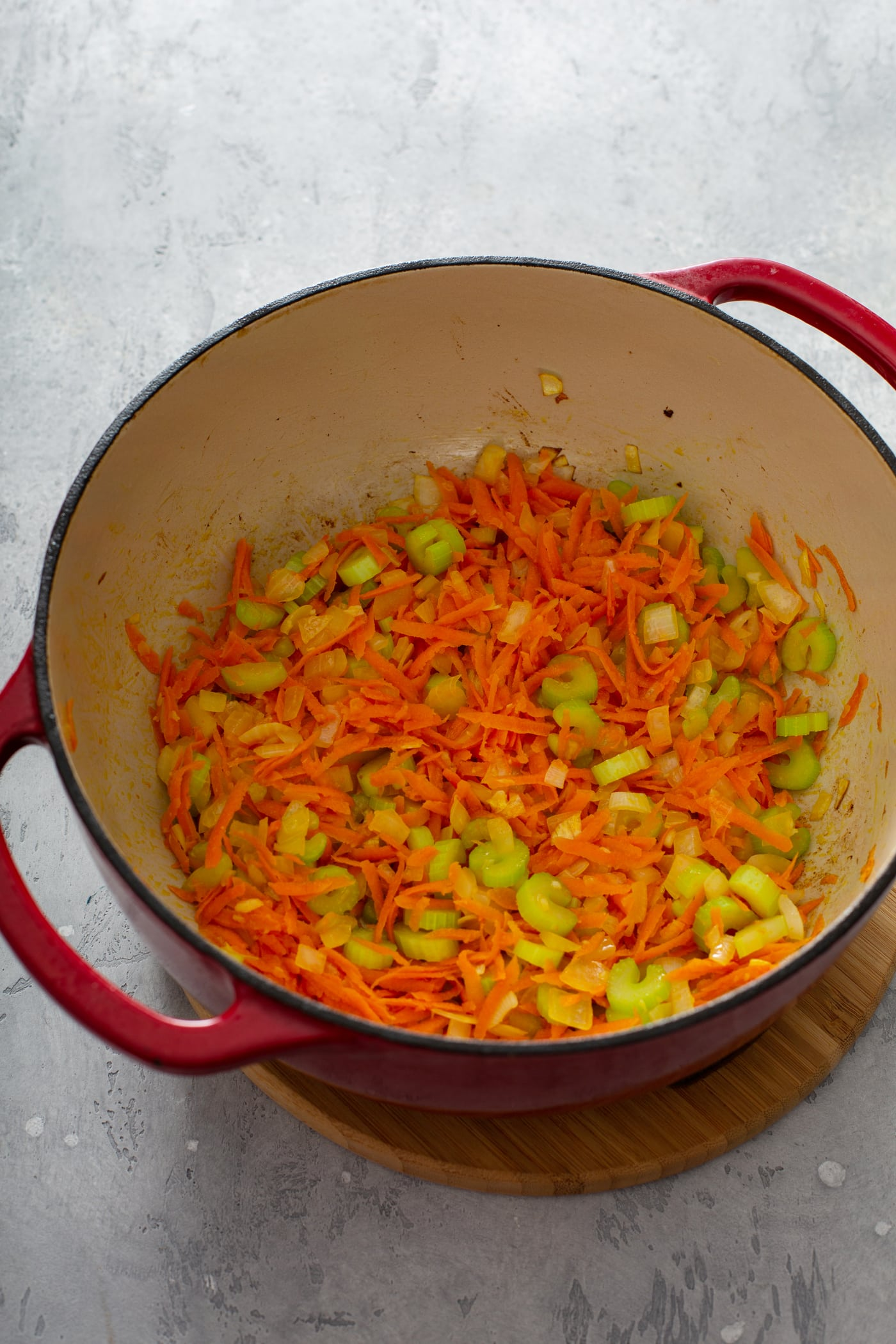 A red soup pot with bright orange shredded carrots and sliced green celery.