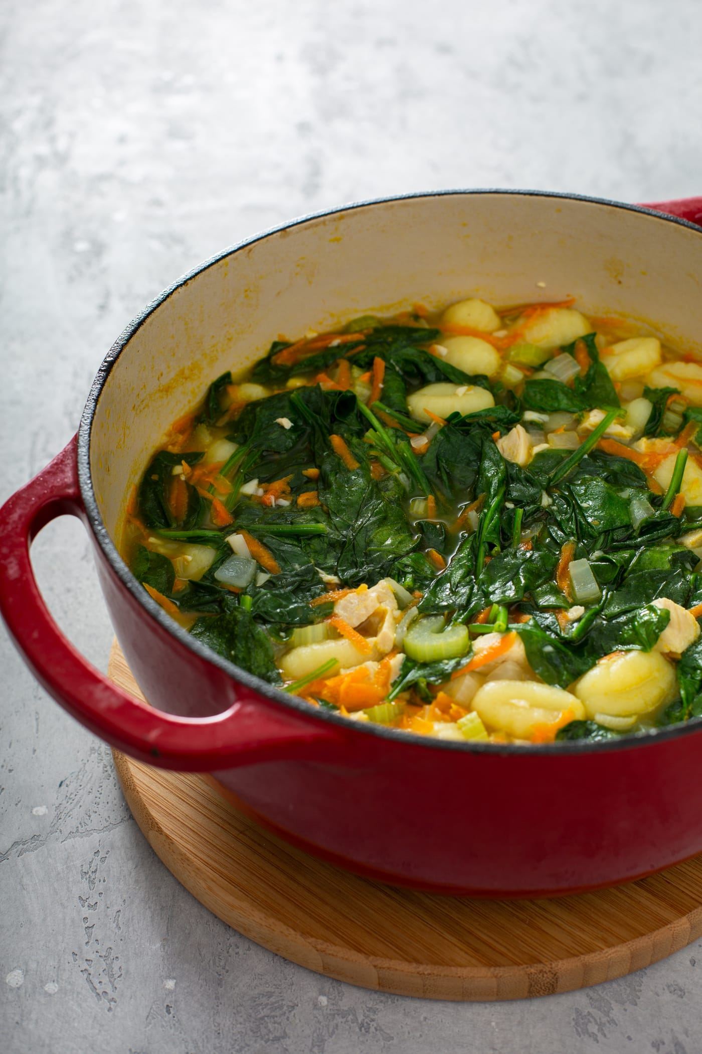 A red soup pot with spinach, gnocchi, shredded carrots, celery, onions and chicken.