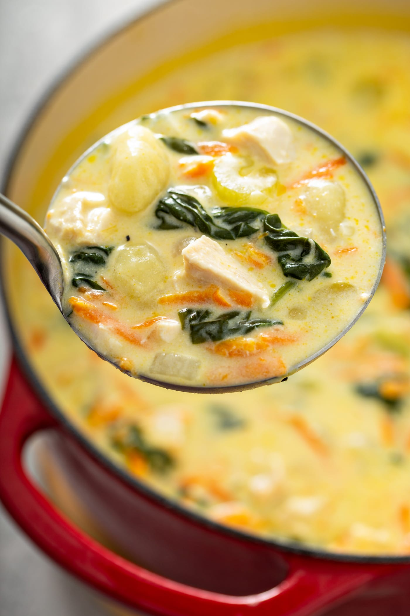A soup pot of Olive Garden chicken and gnocchi soup with a ladle full of soup. There are shredded carrots, chicken, gnocchi, and spinach in a creamy soup.