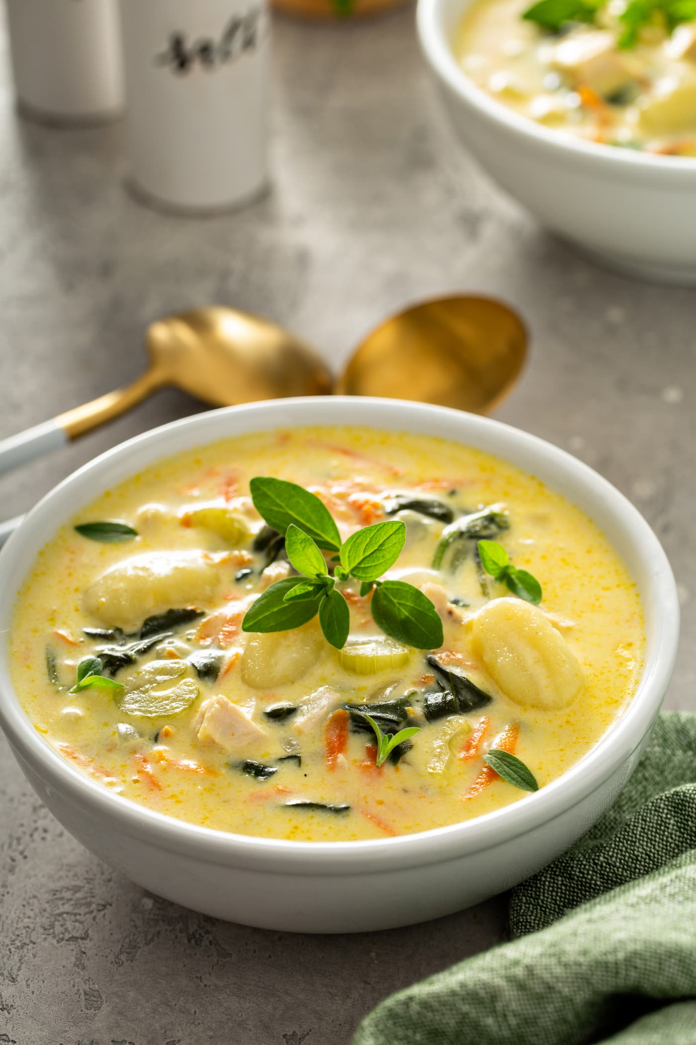 A bowl of copycat gnocchi soup. There are shredded carrots, gnocchi, celery, and chicken in a creamy soup. Two soup spoons are next to the bowl of soup and a sprig fresh herbs tops the soup.