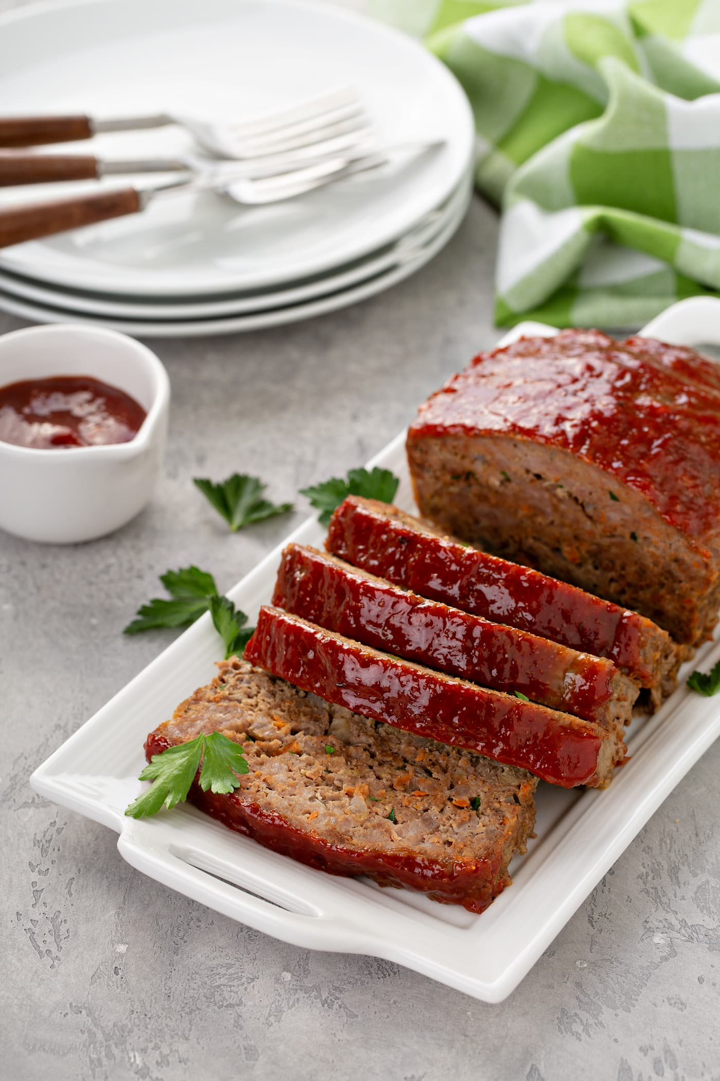 A tray containing a partially sliced meatloaf. There are parsley leaves sprinkled around the meatloaf and a container of glaze beside the tray. There is a stack of white dinner plates with forks on them in the background.