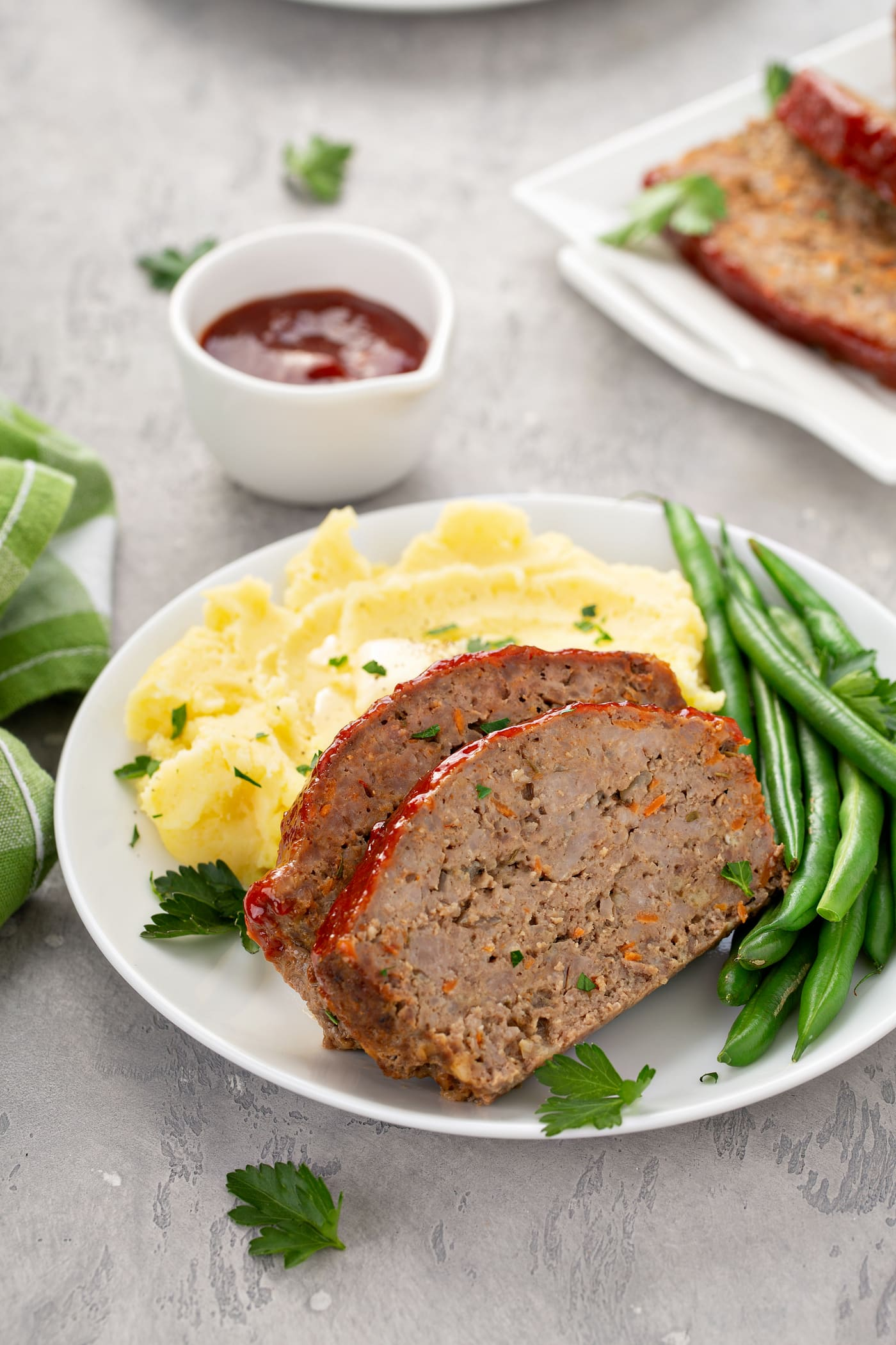 A plate containing two slices of meatloaf, green beans and mashed potatoes. There is a small container of glaze in the background.