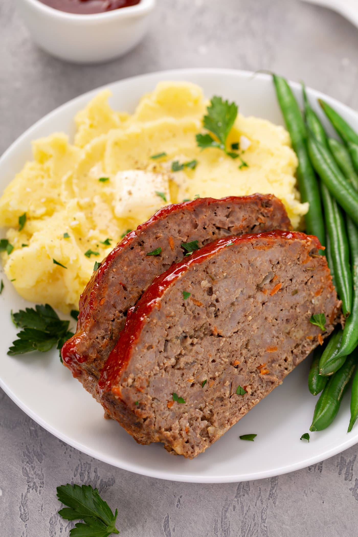 A white dinner plate containing two slices of meatloaf and green beans and mashed potatoes with butter in the middle and sprinkled with parsley leaves.