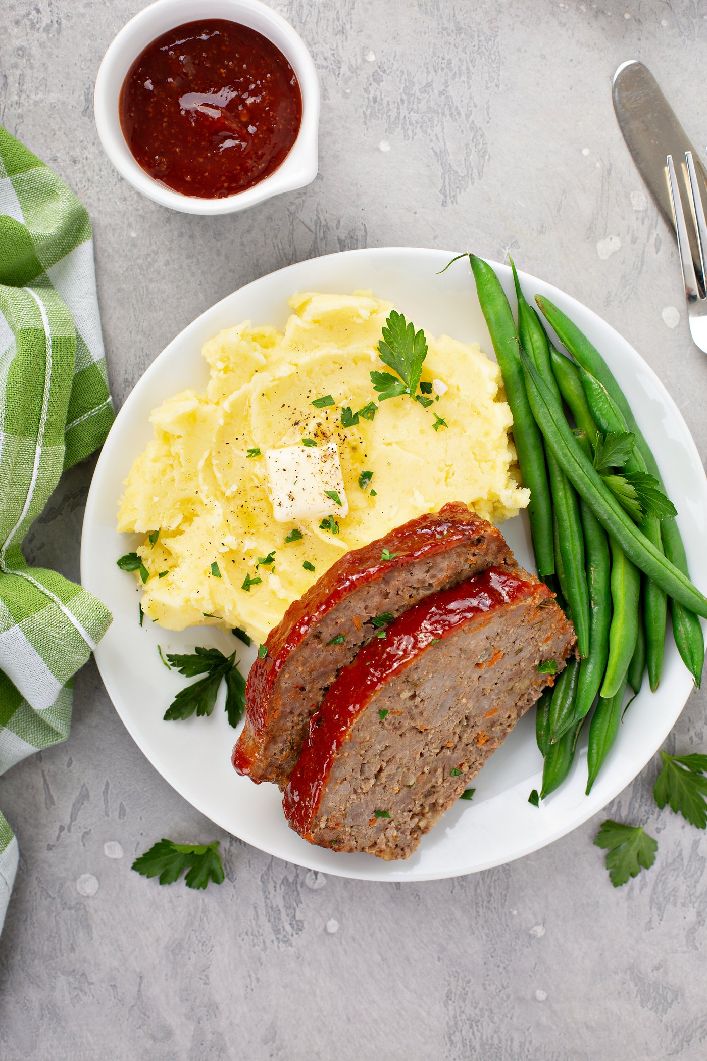 A white dinner plate containing two slices of meatloaf, green beans, mashed potatoes topped with butter, and sprinkled with parsley leaves. there is a green plaid napkin beside the plate and a small container of glaze in the background.
