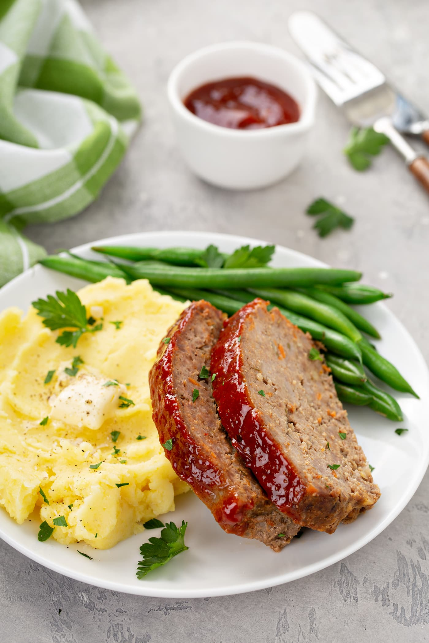 A white dinner plate containing two slices of meatloaf, green beans, mashed potatoes topped with melting butter. A green plaid napkin and a container of red glaze is in the background.