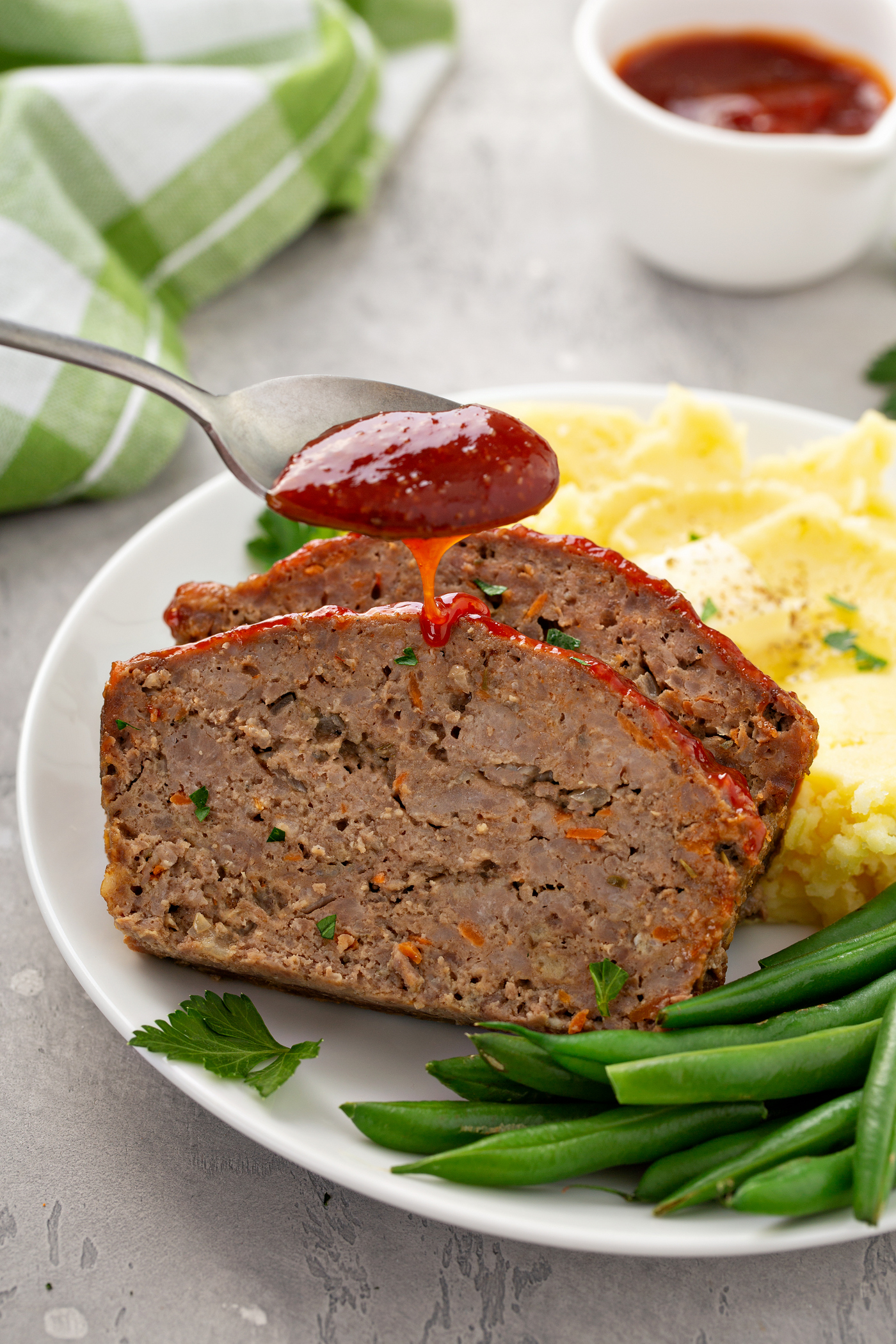 A white dinner plate containing mashed potatoes, green beans, and two slices of meatloaf. A red glaze is being poured from a spoon onto the top of the meatloaf.