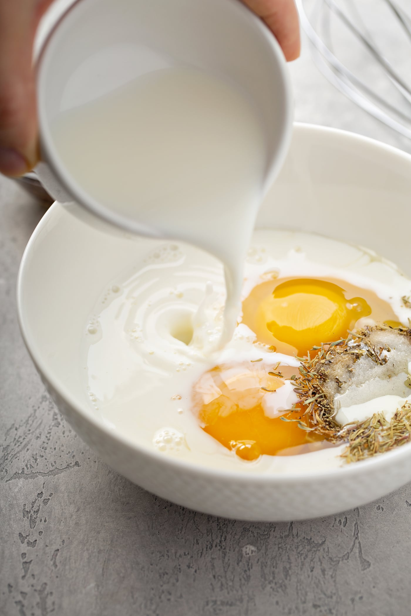 A large bowl containing two eggs, and spices, with milk being poured onto the bowl.