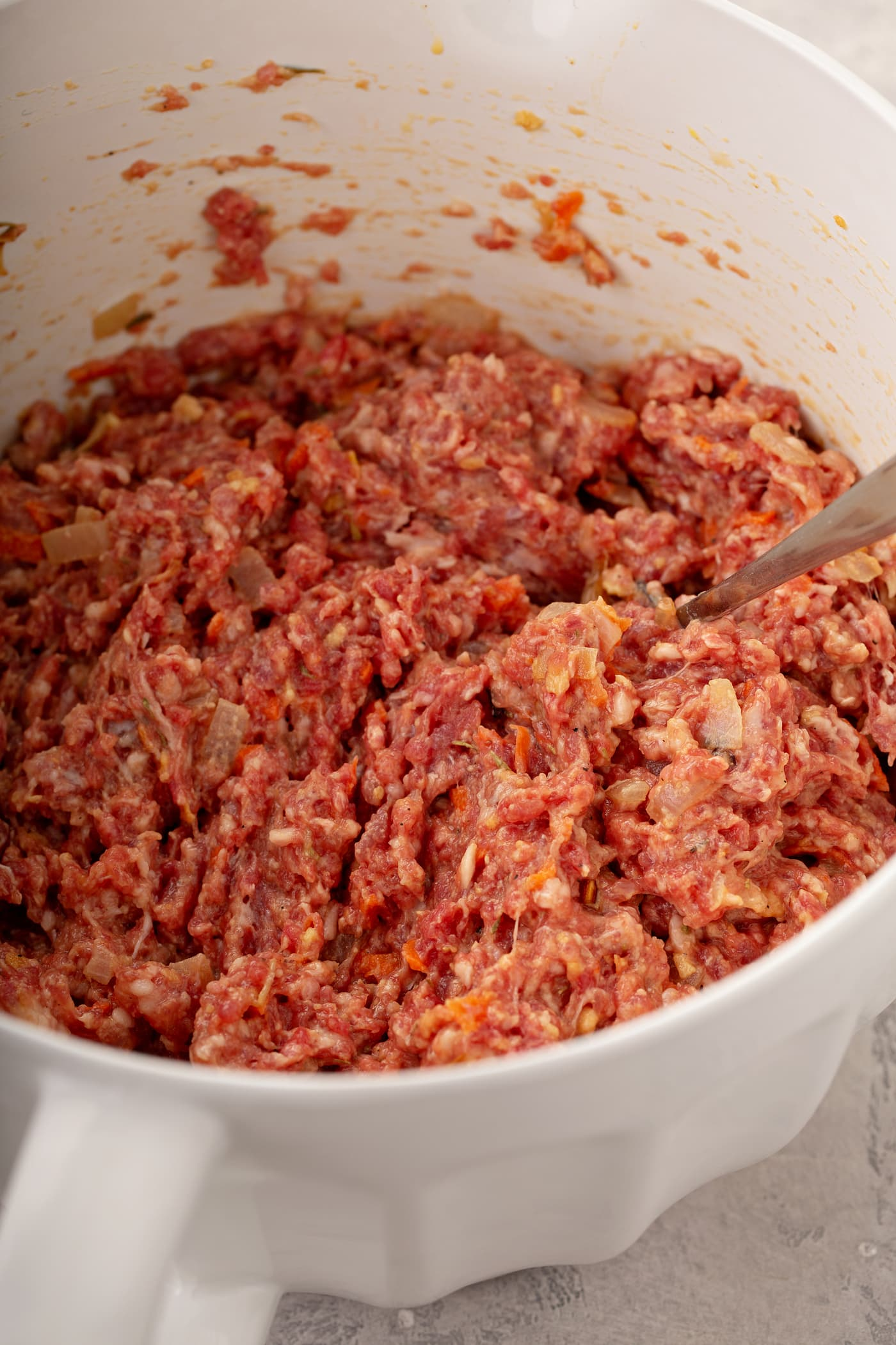 A bowl filled with ground meat. A spoon is in the meat.