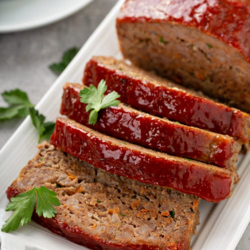 A tray holding meatloaf that has four slices cut, sprinkled with parsley leaves, with a side dish of green beans.