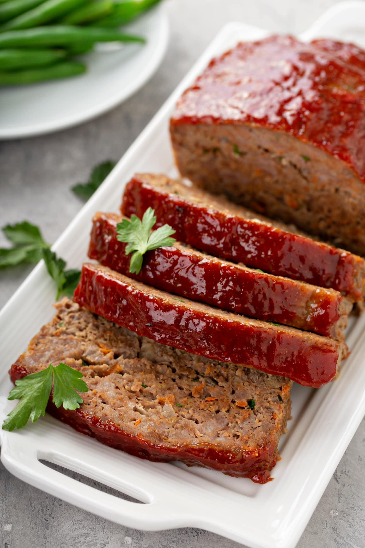 A tray holding meatloaf that has four slices cut, sprinkled with parsley leaves