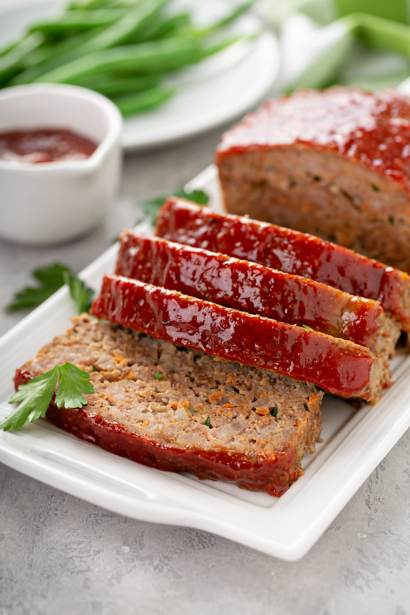 A tray with a partially sliced meatloaf. A small container of glaze sits next to the meatloaf and a plate of green beans is in the background. There are parsley leaves sprinkled around.