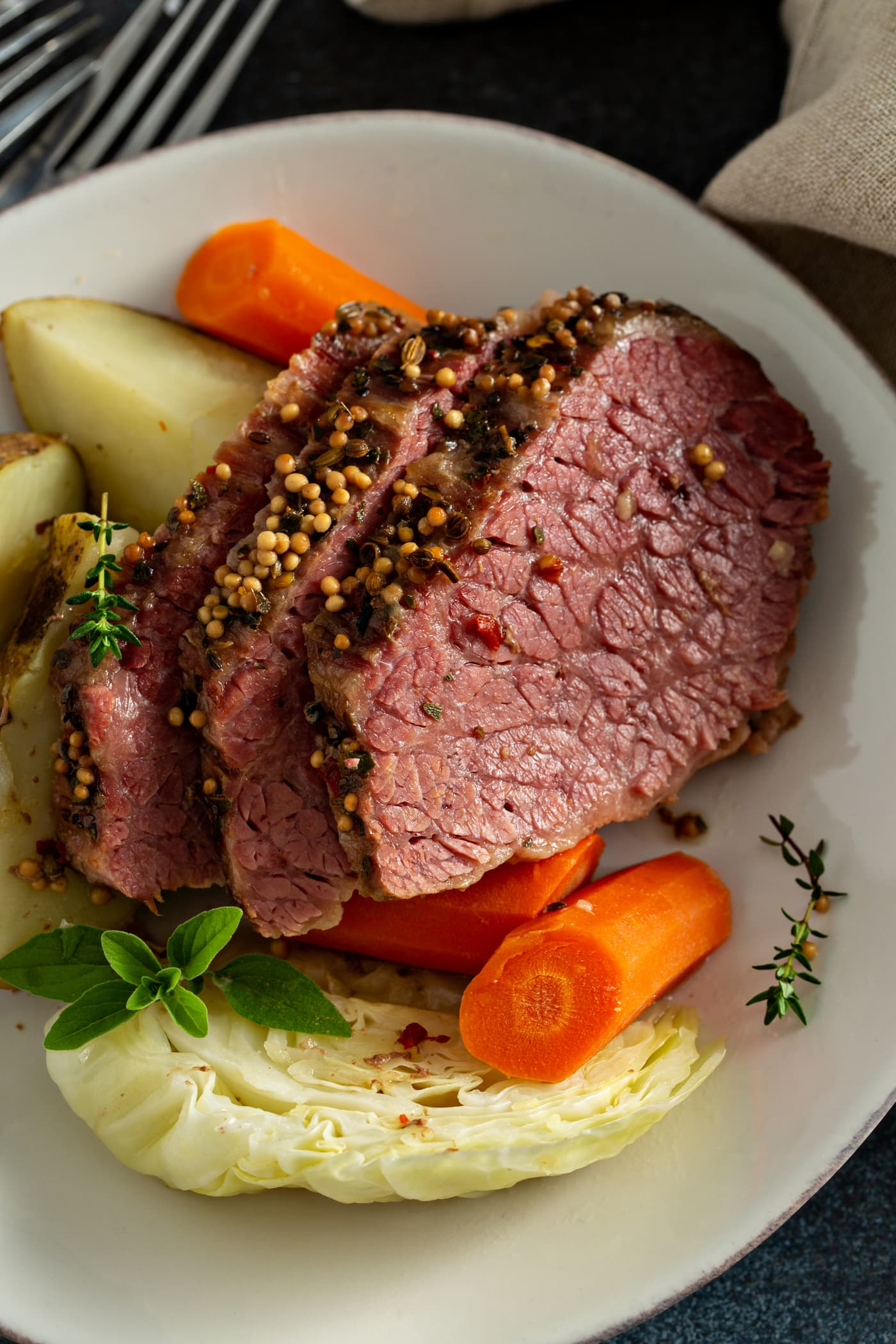 Three slices of corned beef with carrots and potatoes and cabbage on a white plate.