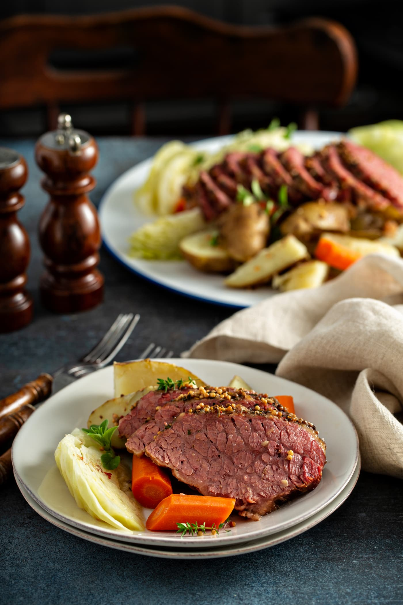 A dinner table with a platter of sliced corned beef and cabbage surrounded by potatoes, carrots, and cabbage. There is a dinner plate with three slices of corned beef and carrots, potatoes and cabbage. There are two forks on the table next to the plate and a wooden salt and pepper shaker in the background. There is also a tan linen napkin bunched up by the plate.