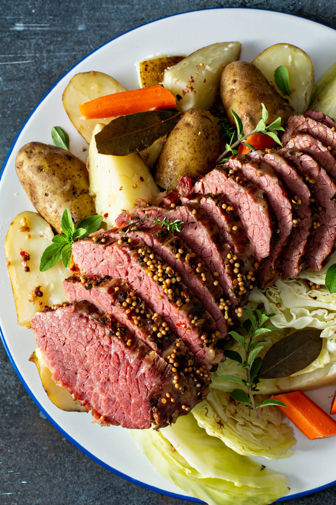 A platter of corned beef and cabbage. There are 12 slices of corned beef with potatoes and carrots on one side and cabbage and carrots on the other side.