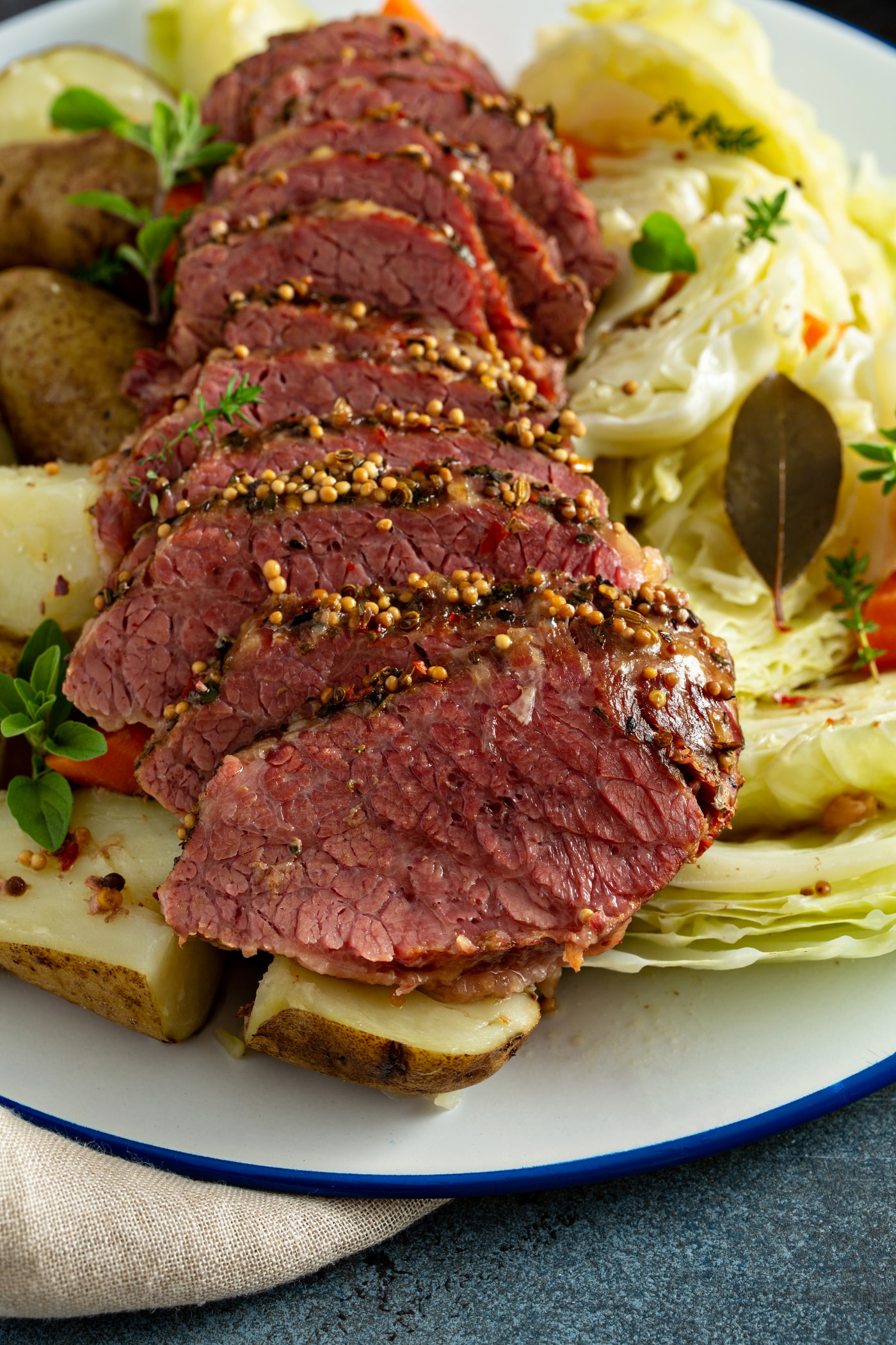 Sliced corned beef laying on top of potatoes, carrots and cabbage.
