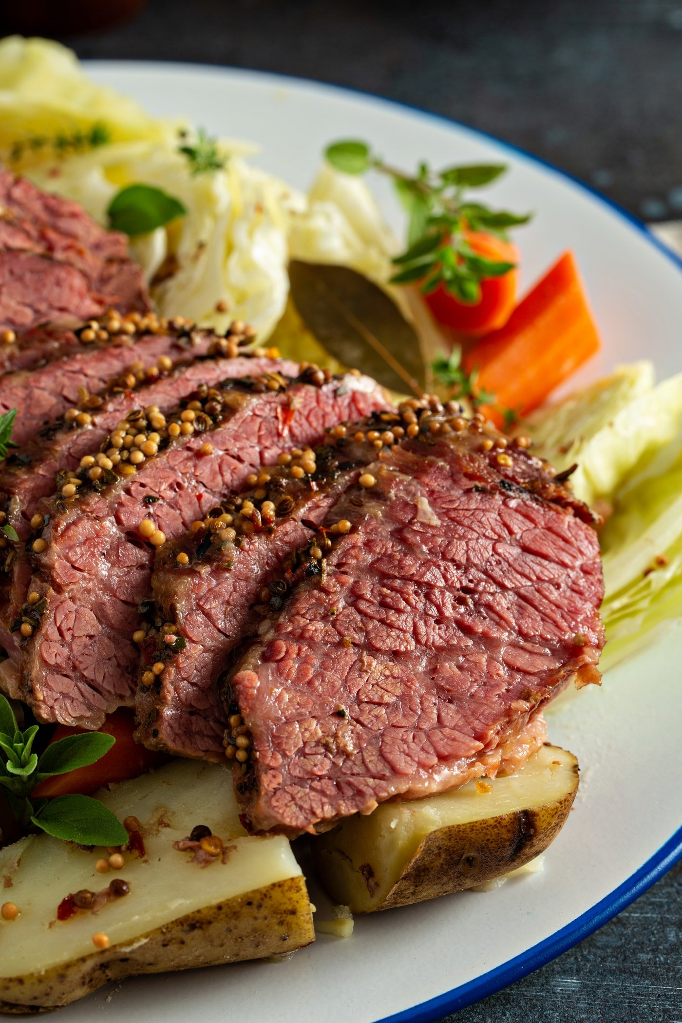 Slice corned beef resting on top of cabbage, potatoes and carrots with sprigs of herbs on the side.