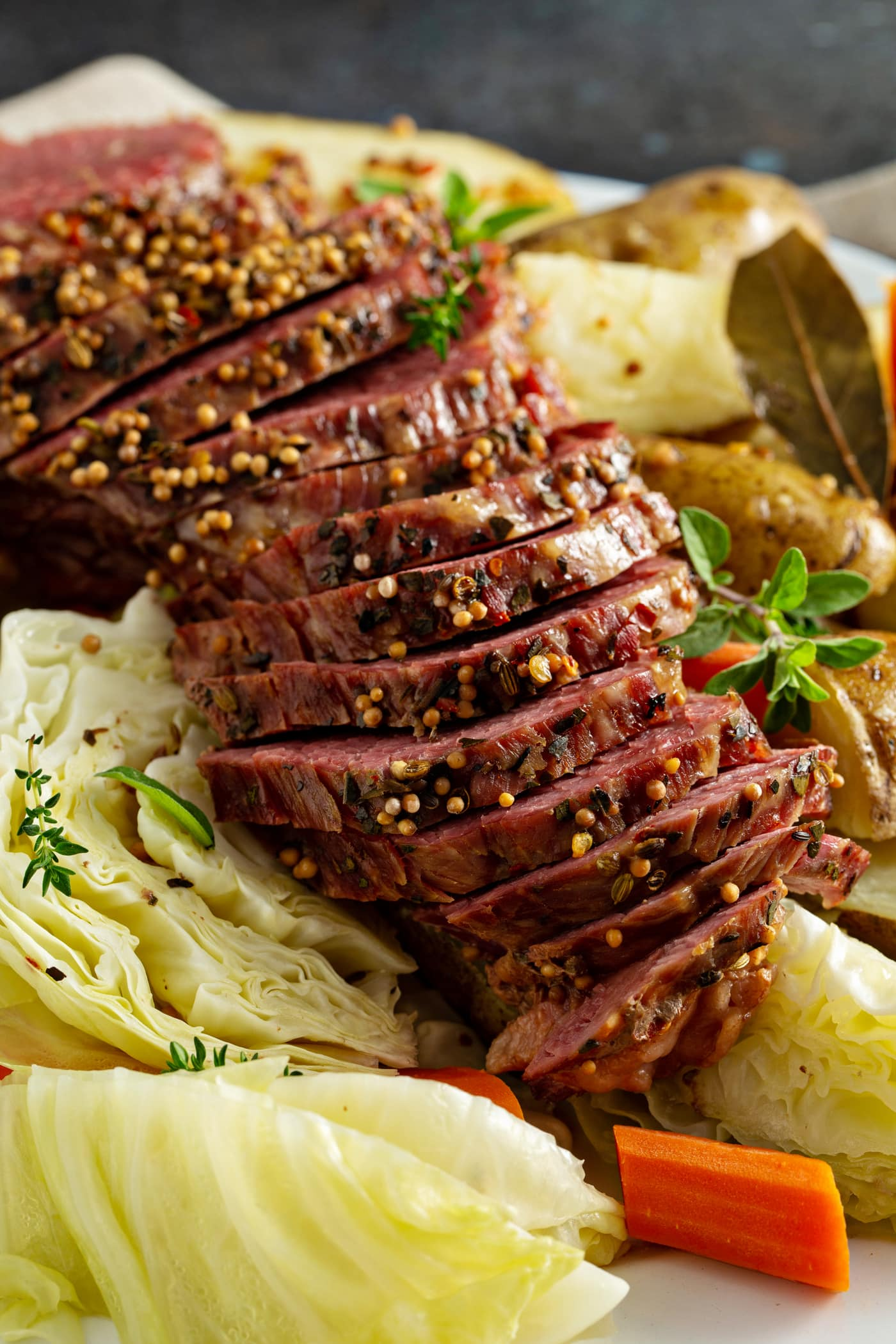 Sliced corned beef resting on top of potatoes and cabbage.