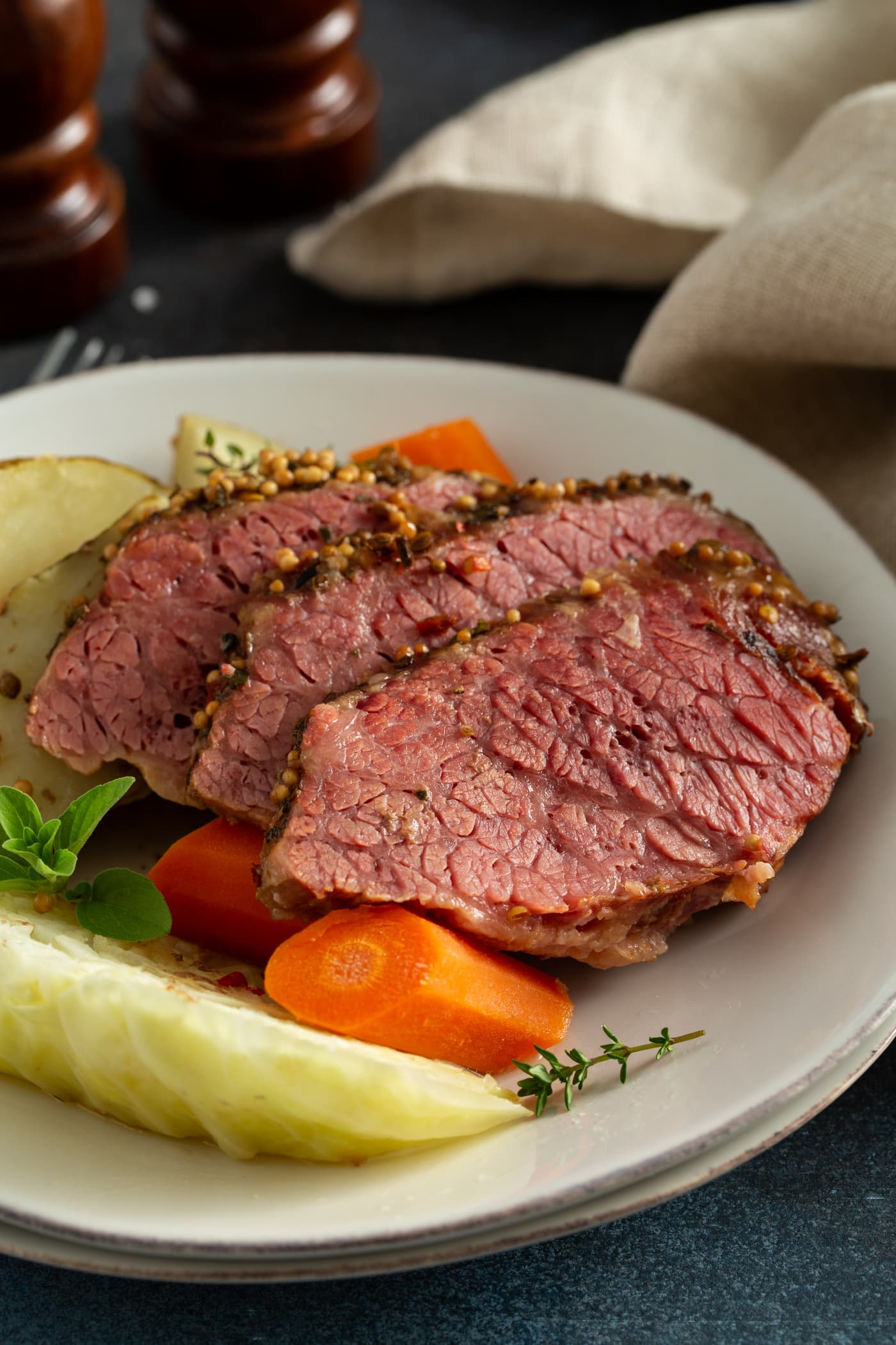 Three slices of corned beef next to carrots and potatoes and cabbage, all on a white serving plate. There are sprigs of green herbs on top.