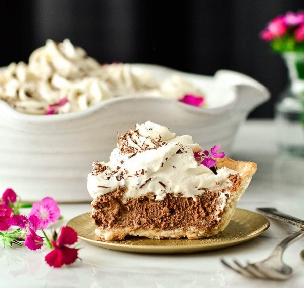 This Homemade French Silk Pie is made completely from scratch! This dessert recipes includes a flaky pie shell that is filled with an irresistibly chocolatey cream filling and topped with homemade whipped cream! The best part? It's even more deliciousthan the infamous version from Village Inn (or Baker's Square)