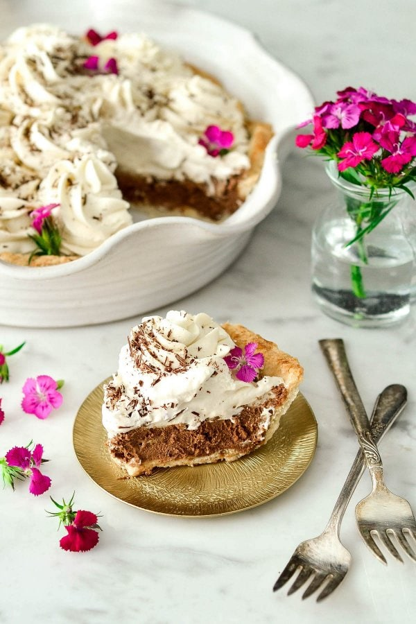 This Homemade French Silk Pie is made completely from scratch! A flaky pie shell is filled with an irresistibly chocolatey cream filling and topped with homemade whipped cream! The best part? It's even more deliciousthan the infamous version from Village Inn {or Baker's Square for my Midwest-dwelling friends}!