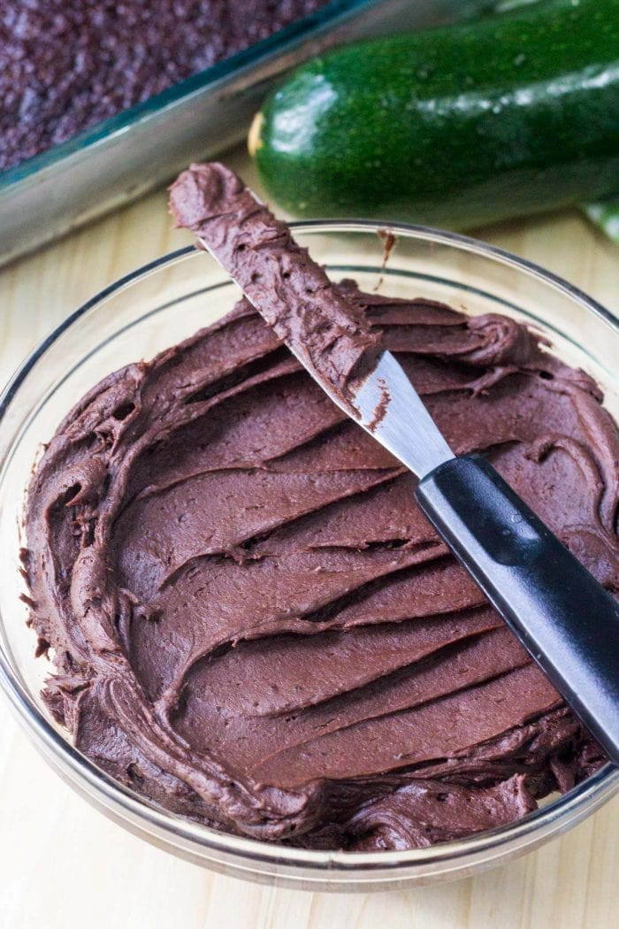 bowl of homemade chocolate frosting with knife resting on top