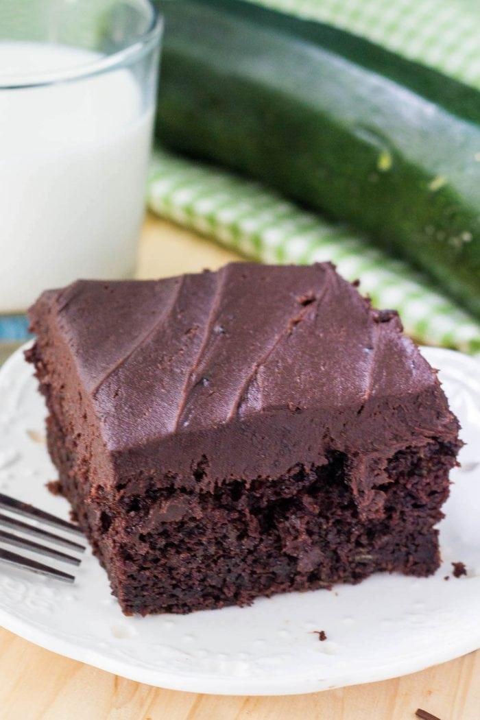 slice of chocolate zucchini cake on white plate next to glass of milk