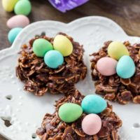 Three Easter Nest Cookies on a white plate topped with miniature eggs.