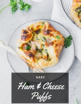 a photo of a golden puff pastries full of cheesy ham and spinach on a circular cooling rack