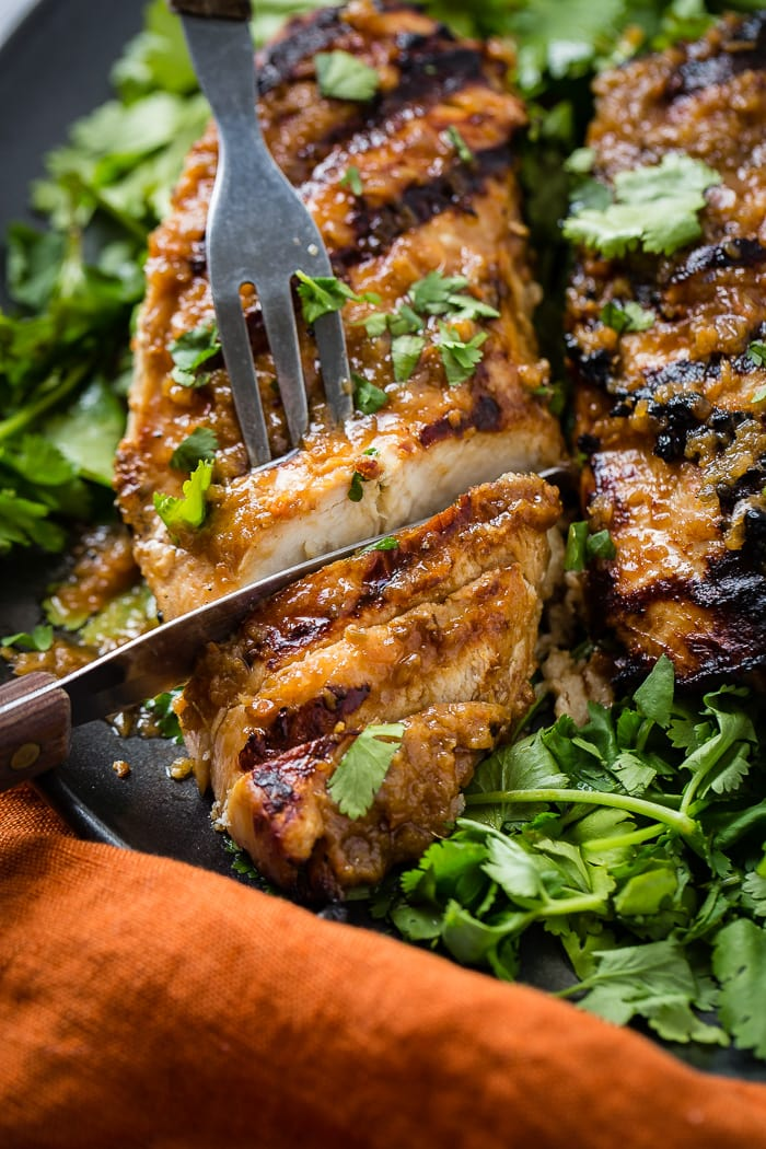 a dark grey platter with a bed of fresh cilantro piled with Asian Ginger Marinade for Grilled Chicken recipe