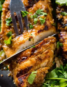 A close up of Asian Ginger Marinade for grilled chicken being sliced with a fork and a knife