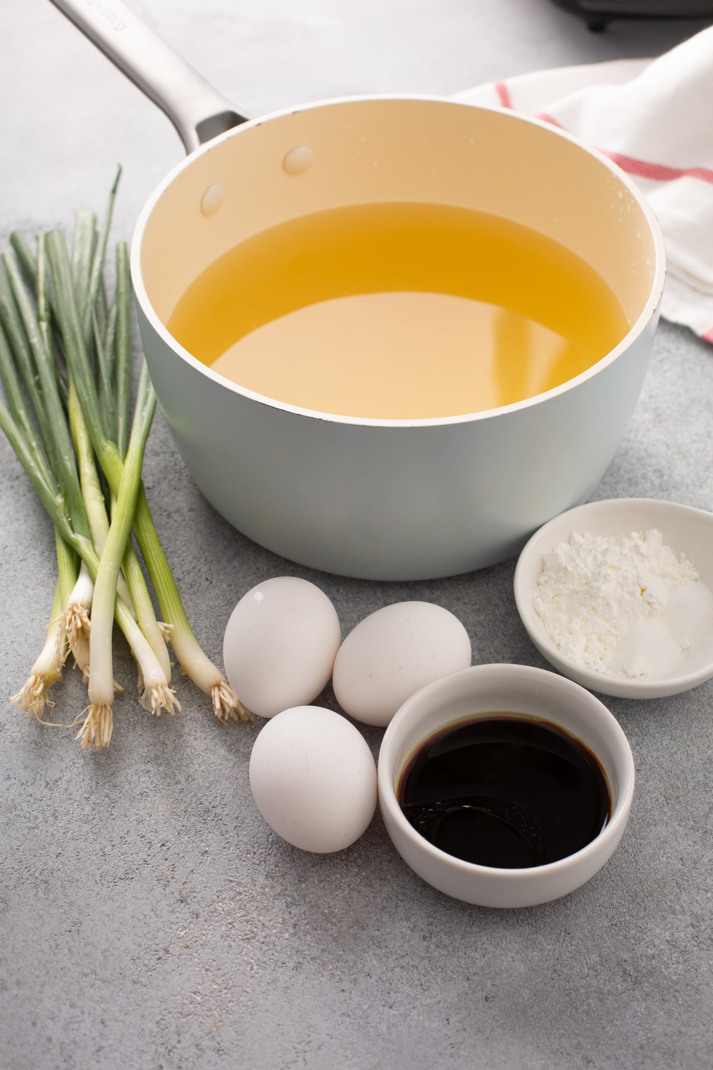 A table top with green onions, three whole eggs, soy sauce, a container of corn starch and a bowl of chicken broth.