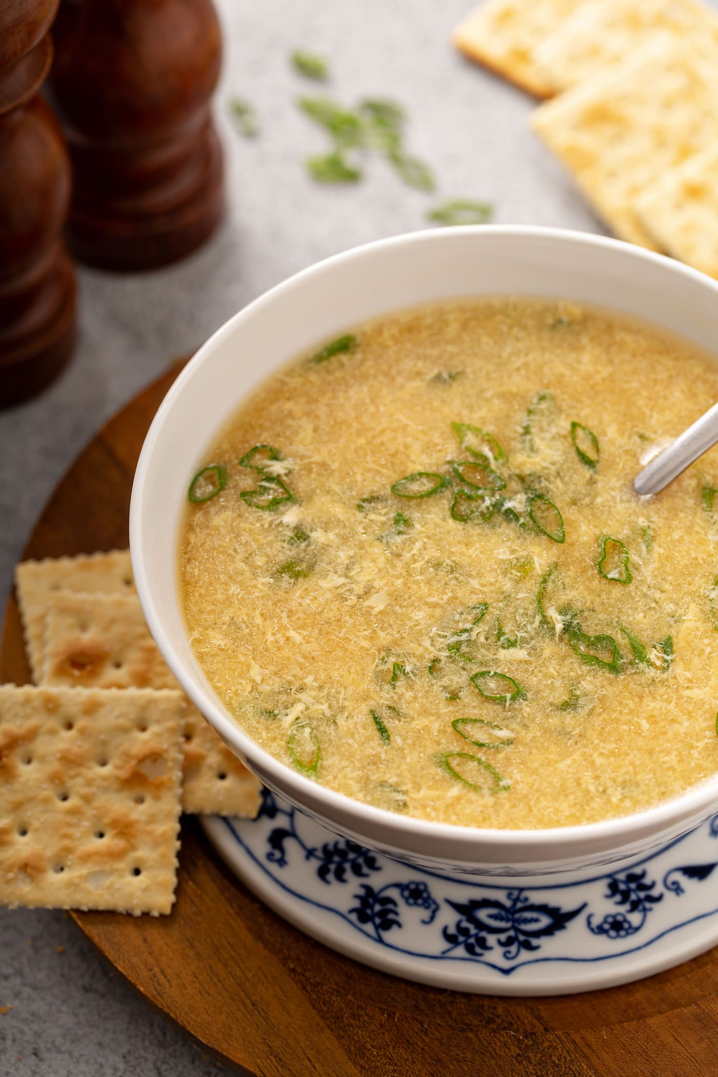 A bowl of egg drop soup with slices of green onion in the soup. Saltine crackers are beside the soup and a salt and peppers shaker is in the background.