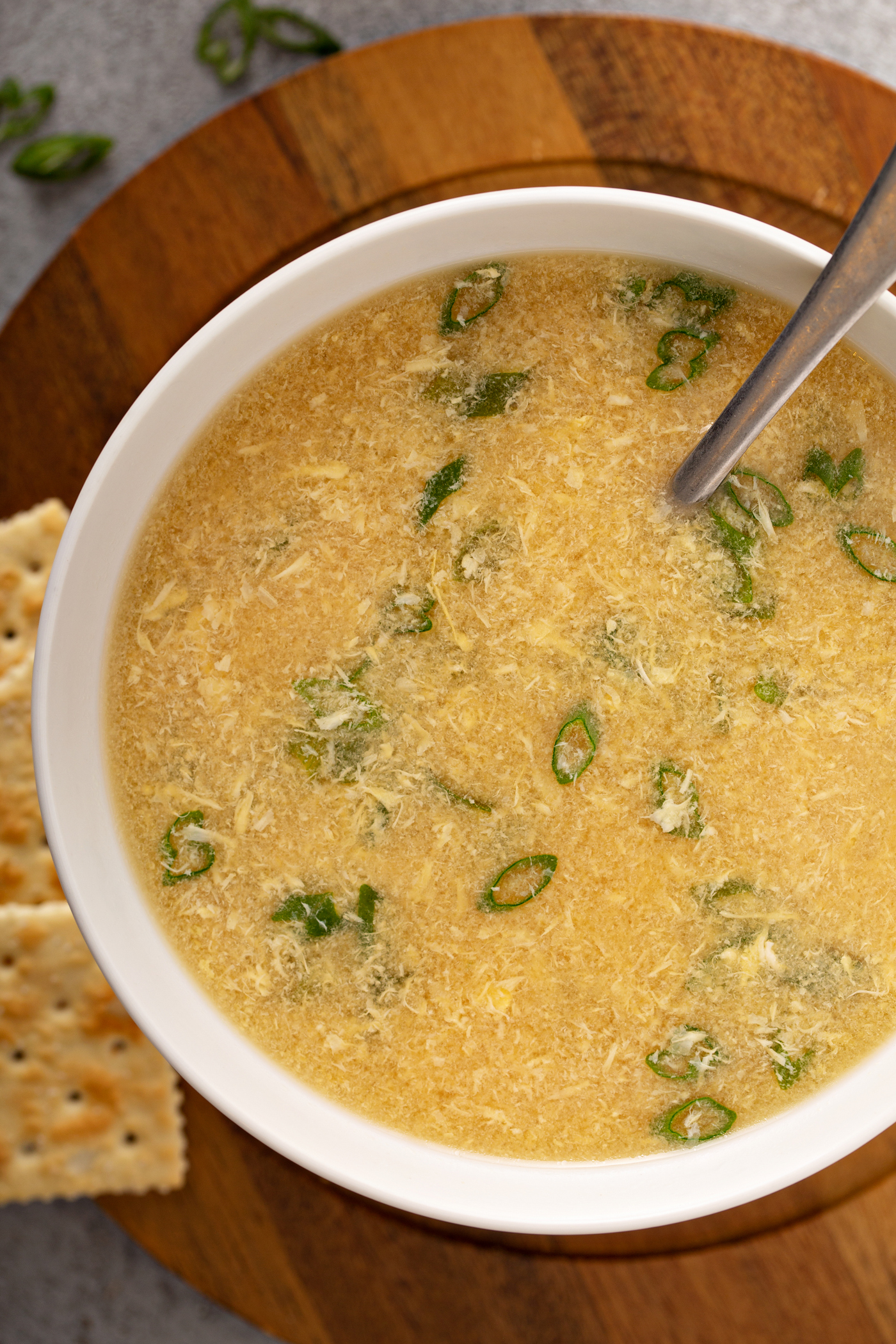 A close-up of a bowl of egg drop soup with sliced onions on top and saltine crackers in the background.