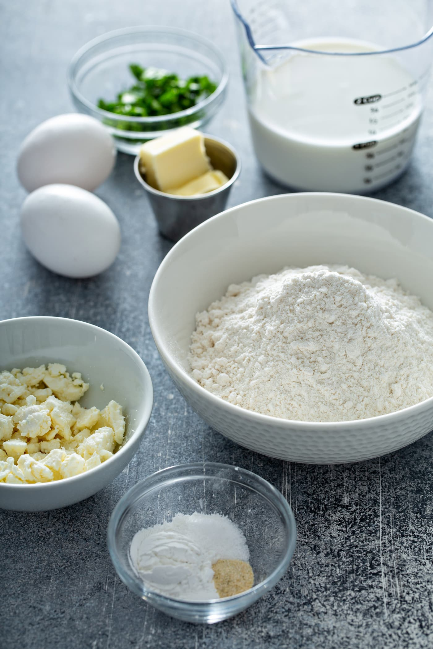 A table top with containers of Flour, feta cheese, butter, salt, green herbs and two white eggs.