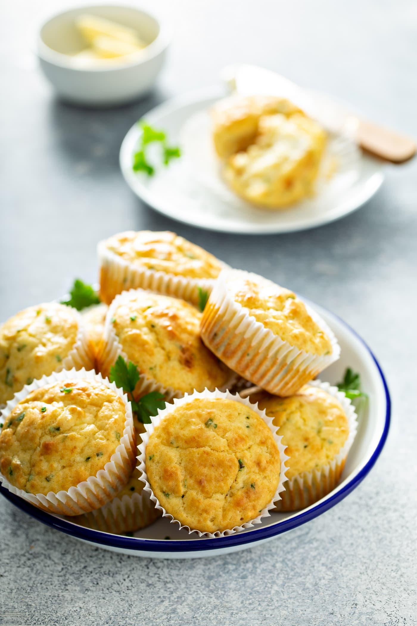 A serving bowl of feta muffins stacked on top of each other. There is a plate with a muffin that is broken in half in the background.