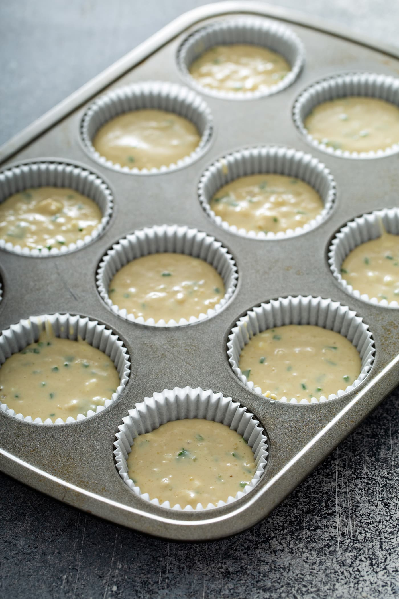 A muffin tin with muffin batter in white paper muffin liners.