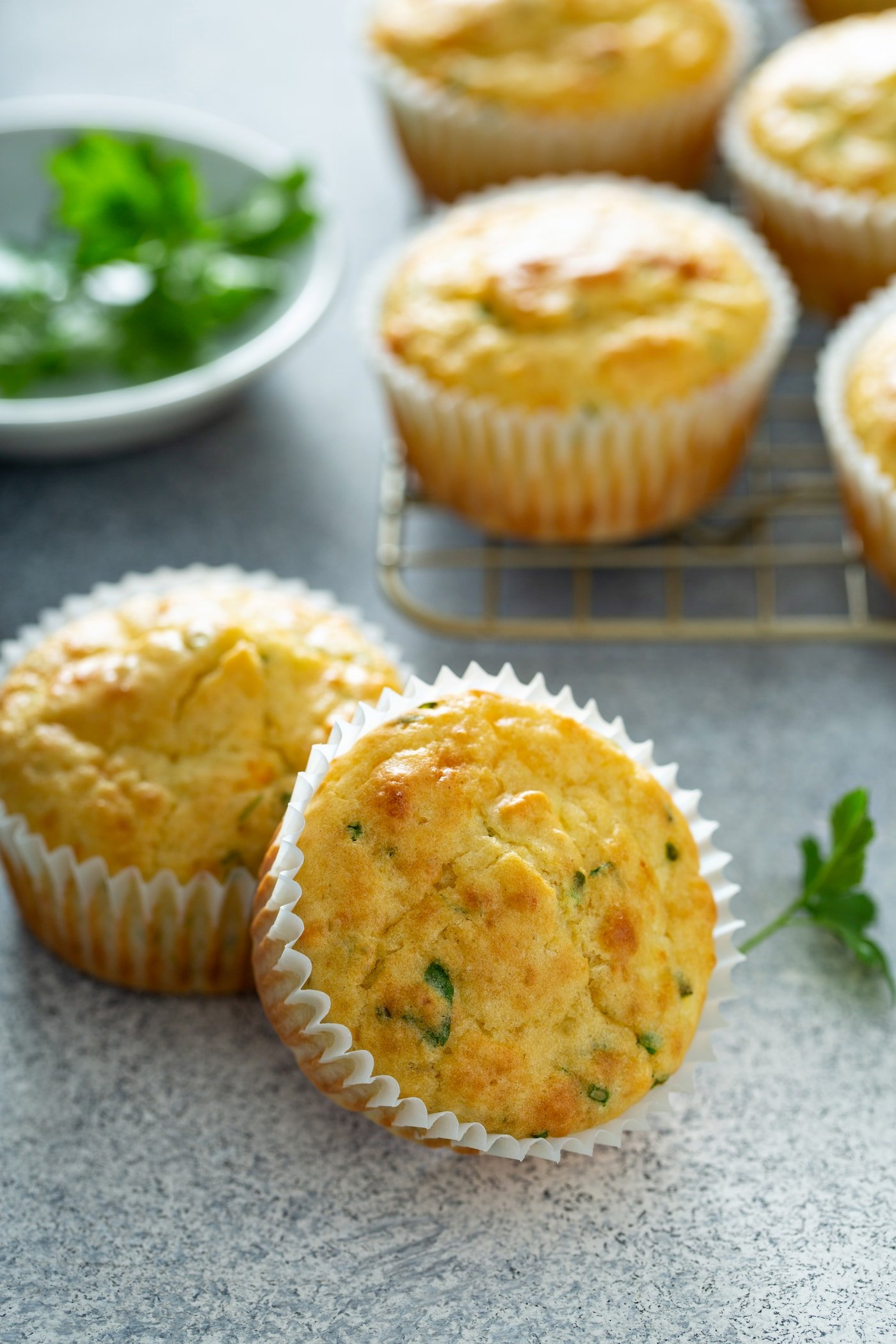 Four baked feta muffins in white paper liners. There is a bowl of chopped parsley and chives in the background.