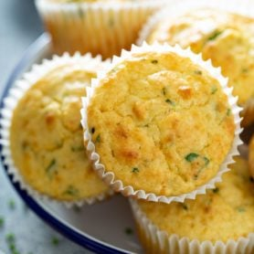 A plate of feta muffins in white muffin liners. The herbs in the muffins are visible.