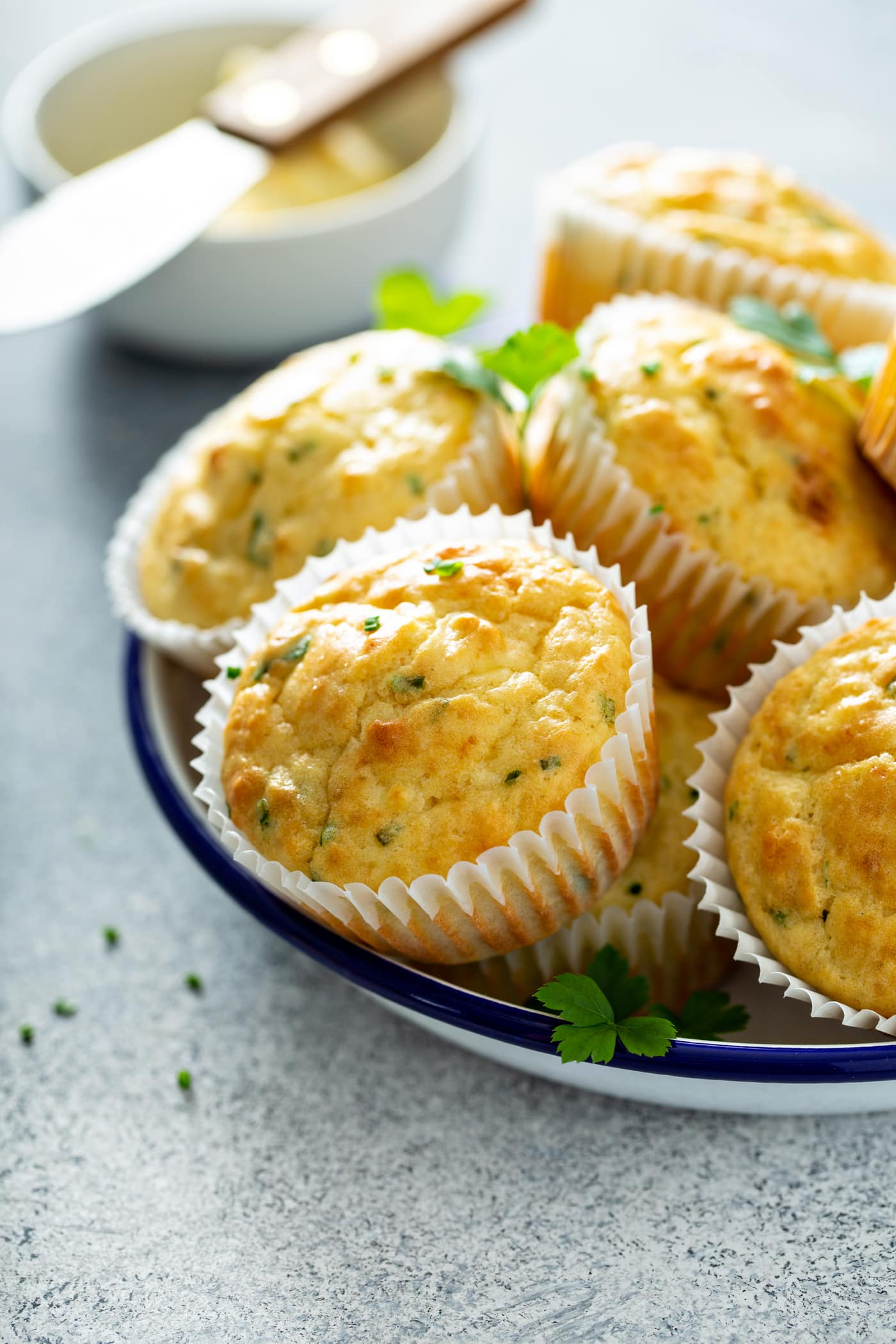 A plate of feta muffins in white paper muffin liners. There are a few parsley leaves on top.
