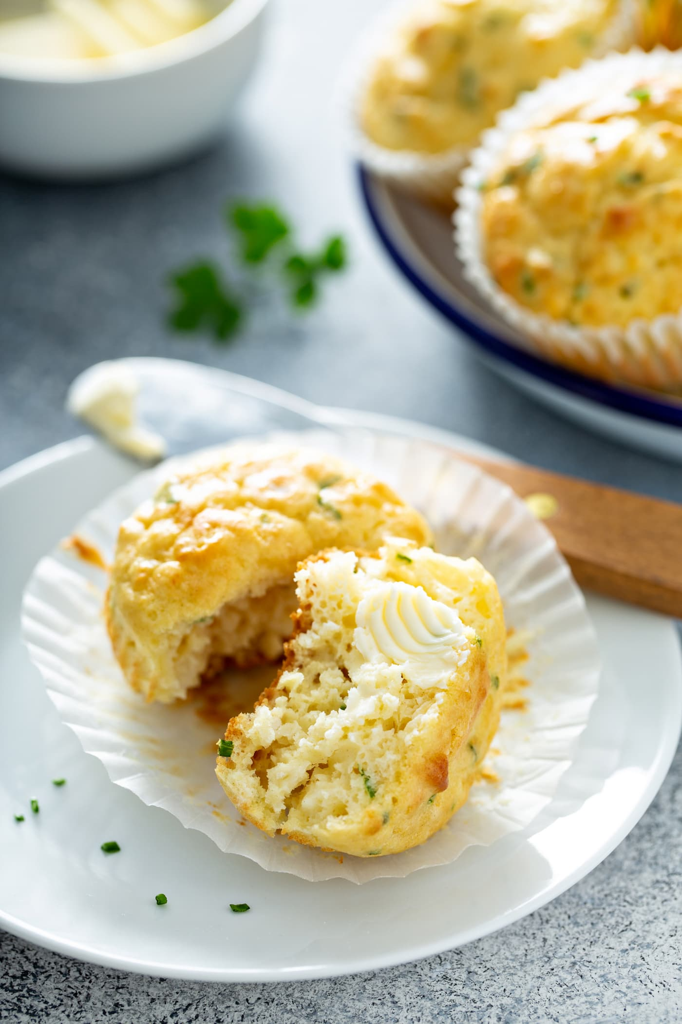 A muffin on a plate. The paper muffin liner is peeled back and the muffin is broken in half showing the herbs inside. A pat of butter is on one half of the muffin. There is a butter knife resting on the plate that the muffin is on. There is a plate of muffins in the background.