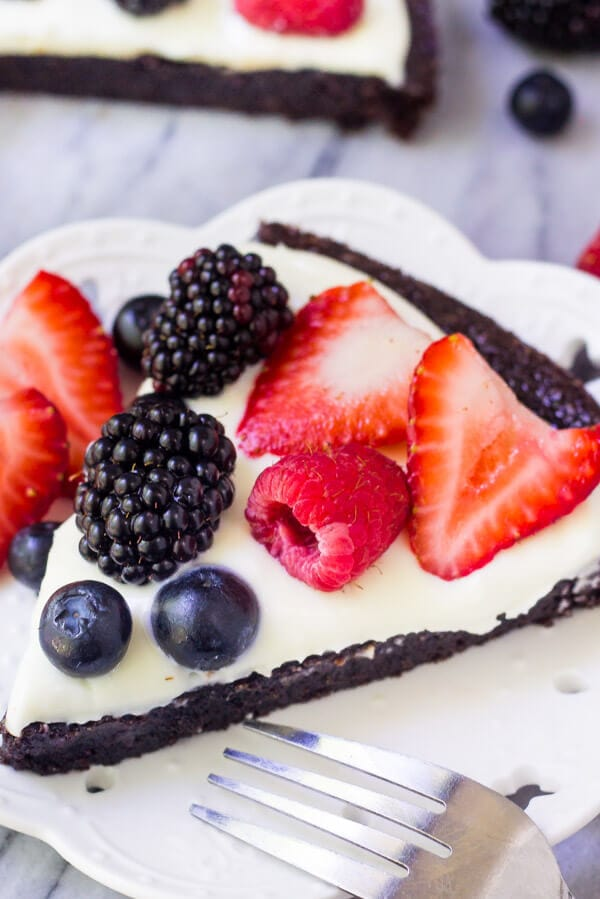 This Very Berry Brownie Pizza is twist on classic brownies that's perfect for summer. It starts with a fudgy, one bowl brownie. Then it's smothered in a sweet cream cheese topping and decorated with fresh berries. If you love fruit pizza & chocolate – then this is the ideal recipe for you.