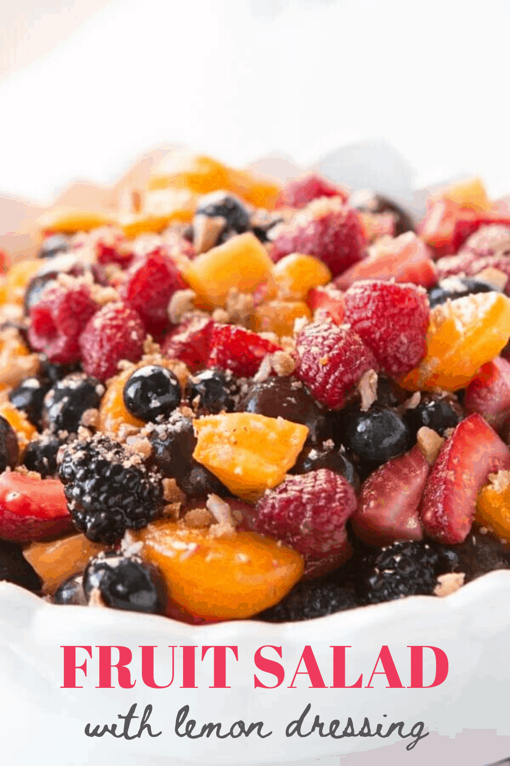 A bowl of fruit salad with blackberries, strawberries, blueberries and mandarin oranges with lemon dressing