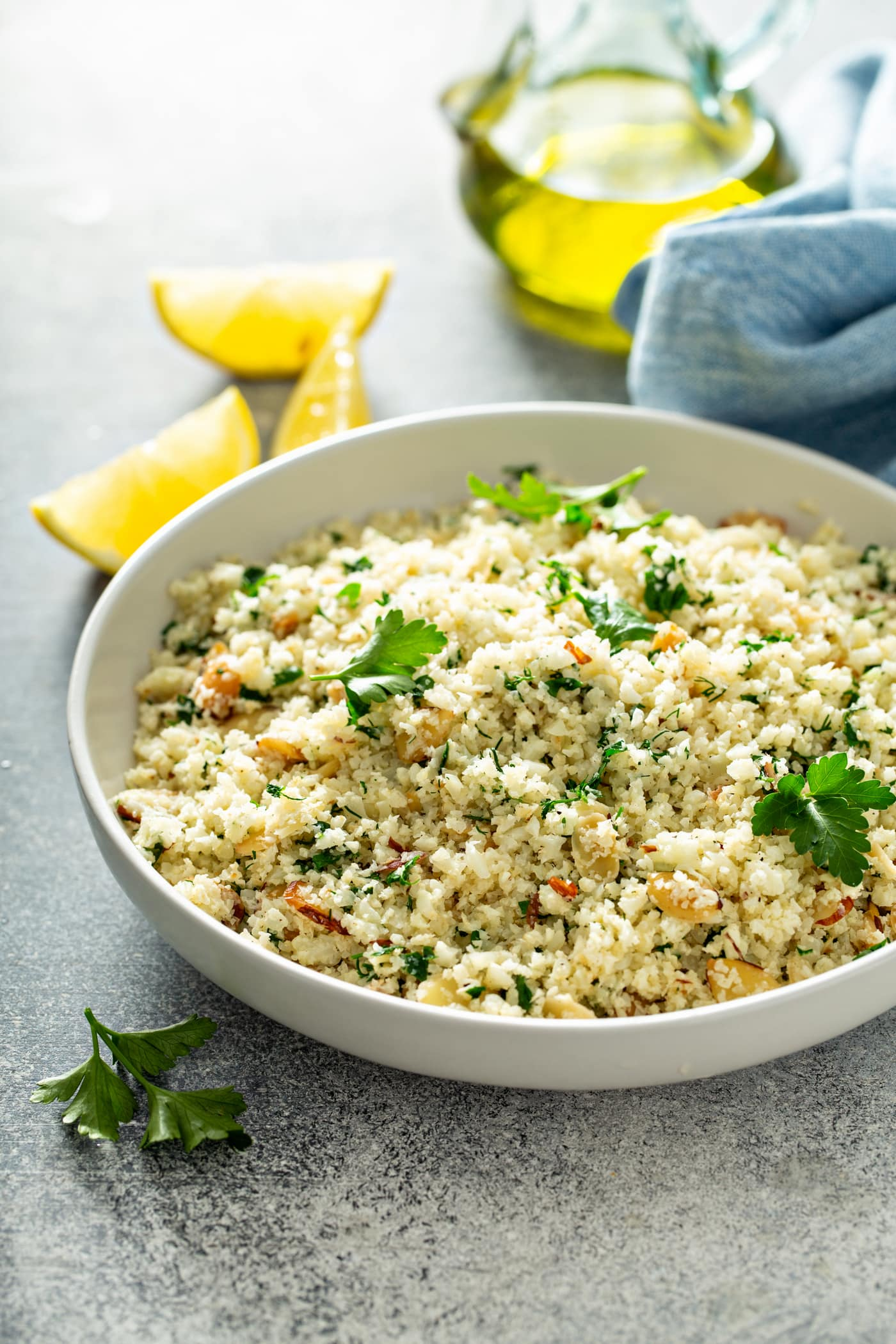 A white serving bowl containing garlic herb cauliflower rice. There are green herbs, garlic and sliced almonds in the rice. Parsley leaves are scattered on top of the rice. There are four lemon wedges next to the bowl of rice.