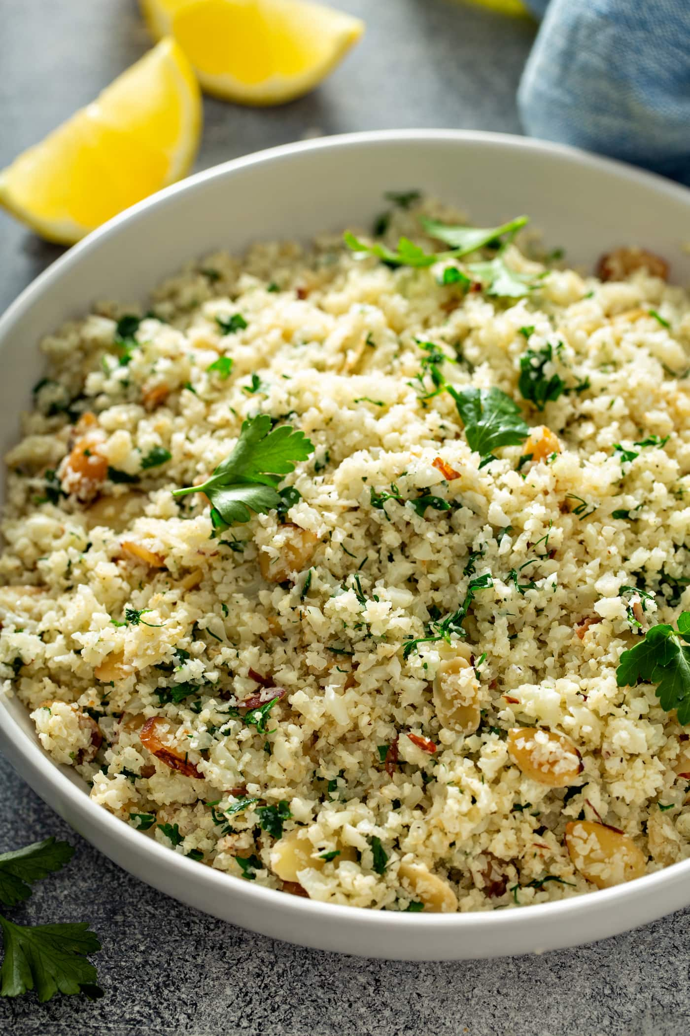 A close-up of a bowl of garlic herb cauliflower rice. There are green herbs, garlic and sliced almonds in the rice, and fresh parsley leaves scattered on top. There is a lemon wedge in the background.