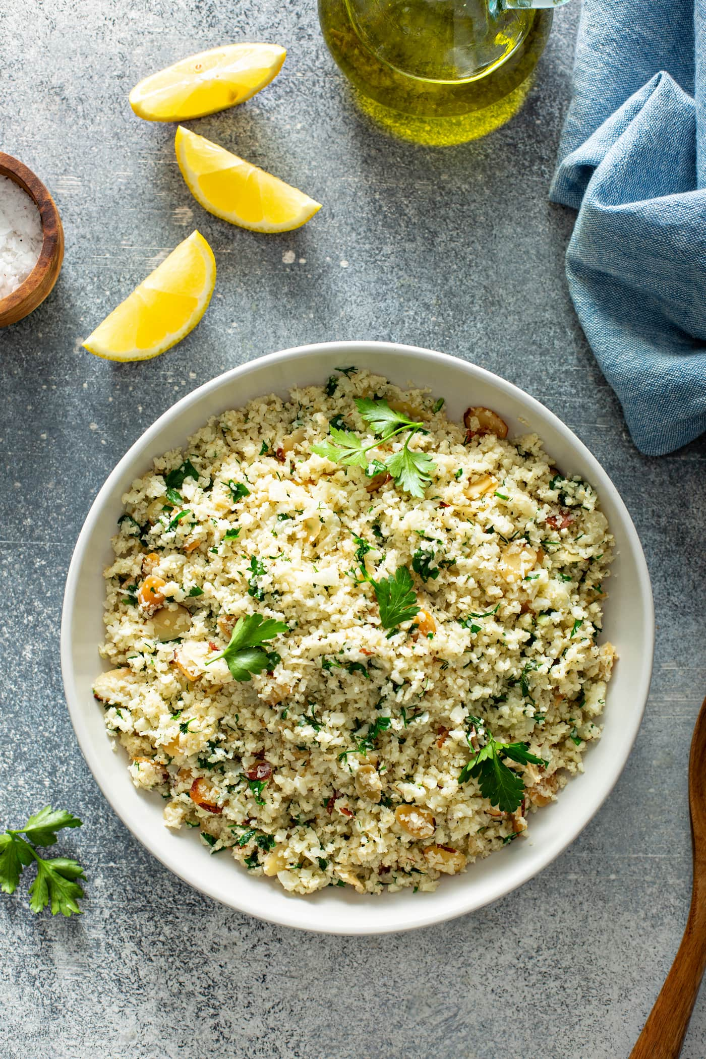 A white serving bowl filled with garlic herb cauliflower rice. There are green herbs and sliced almonds in the rice. There is a container of salt and several lemon wedges and a blue linen napkin in the background.
