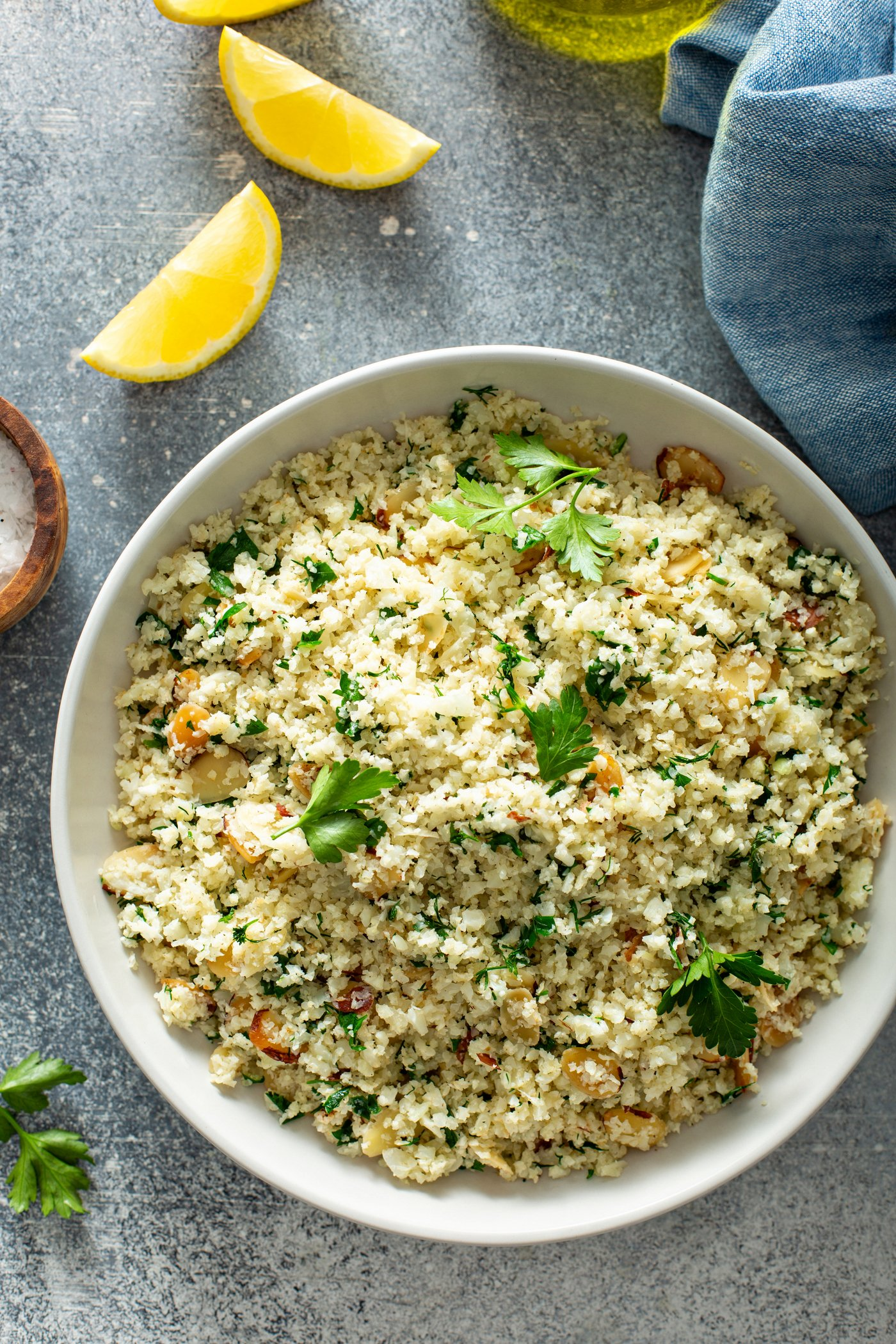 A white serving bowl of garlic herb cauliflower rice. It is topped with fresh parsley leaves. There are lemon wedges, a small container of salt and a blue napkin in the background.